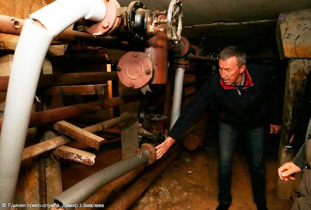 Временно исполняющий обязанности главы Сергиева Посад Юрий Потякин проверяет, теплы ли трубы.
