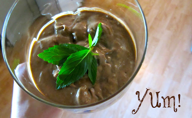 hand holding a glass cup of avocado chocolate pudding with fresh mint leaves on top