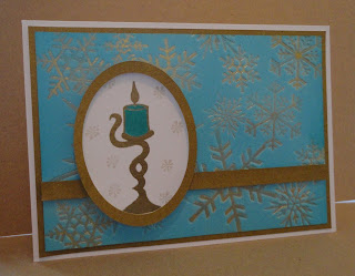 Christmas card in turquoise and gold with candle and snowflake background