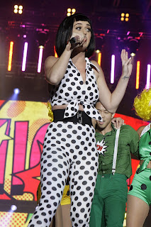 Katy Perry wearing a black wig and 50' inspired outfit