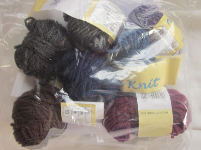 seven small balls of wool in shades of blue, purple and grey