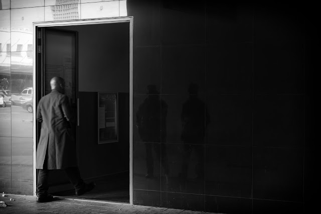 A man moves through a door. Shadowy figures are reflected.
