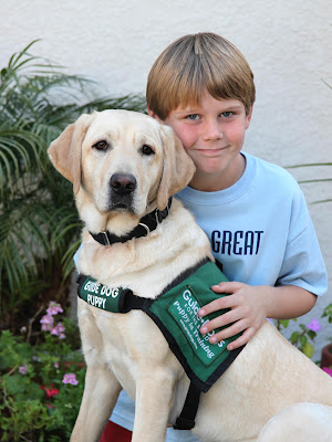 Jimmy Garrison sits with Guide Dog puppy in training Khaki at Jimmy's birthday party. Photo by Pat Whitehead.