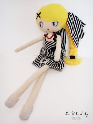 Muñeca de tela con vestido y bolso.