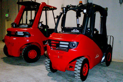 2 brand new orangy red Linde forklifts straight out of the box.