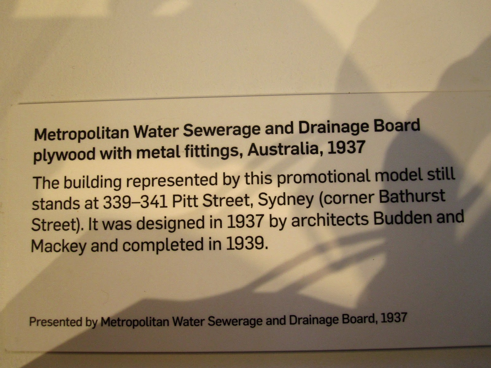 Exhibition sign for the model of the Metropolitan Water Sewerage and Drainage Board building.