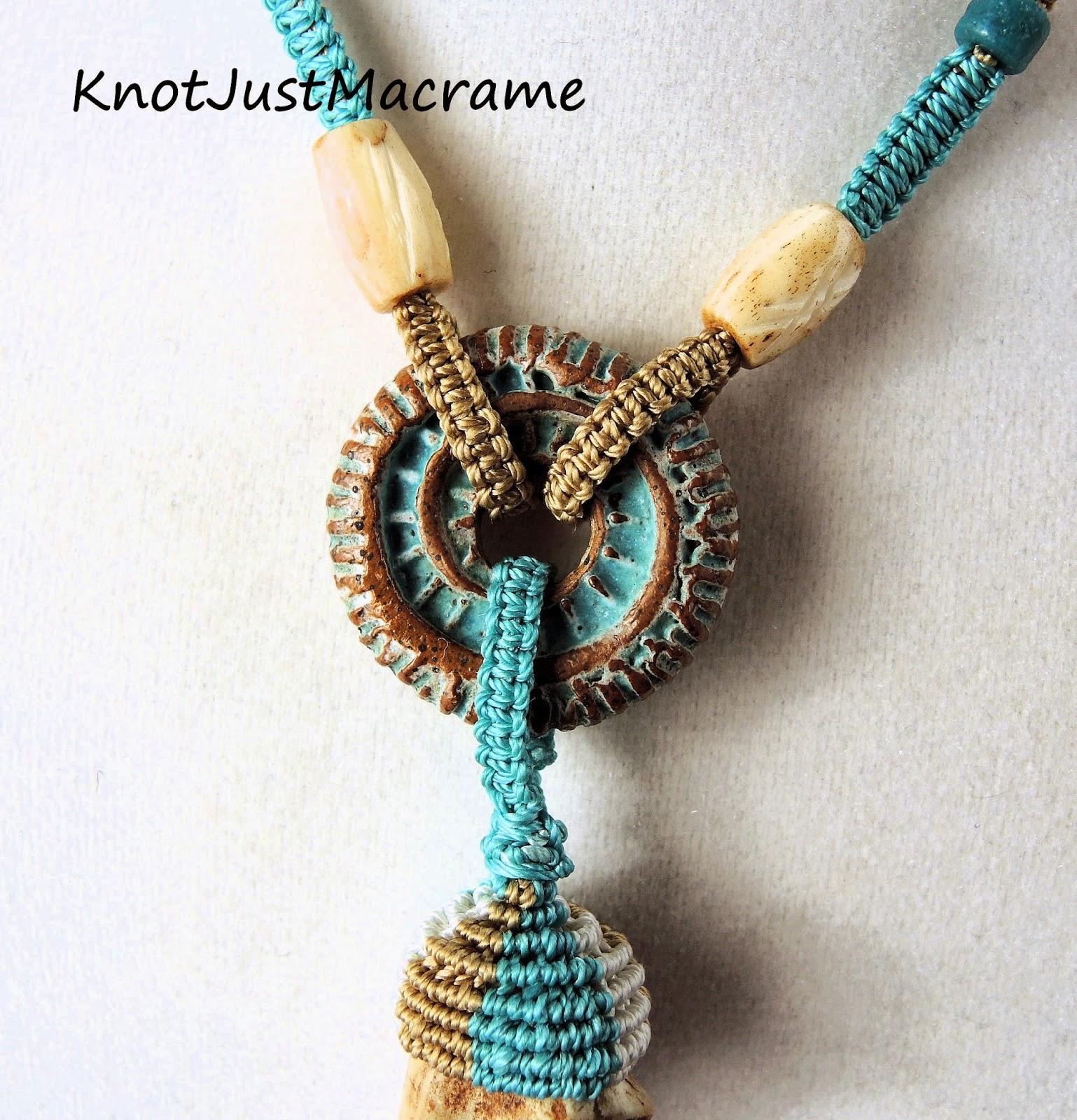 Macrame knotting attached to cermamic spiral fossil disc by Karren Totten.