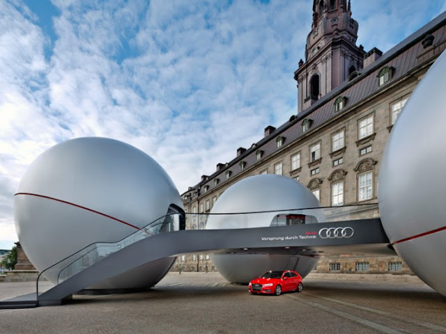 Modern Audi Sphere pavilion with red car