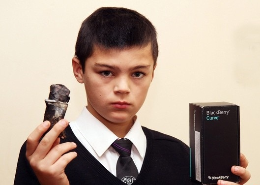 Kian McCreath menunjukkan telefon Blackberry milik abangnya yang meletup.