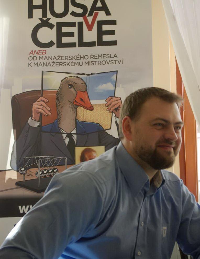 portrét Pavla Kučery s plakátem ke knize Husa v čele
