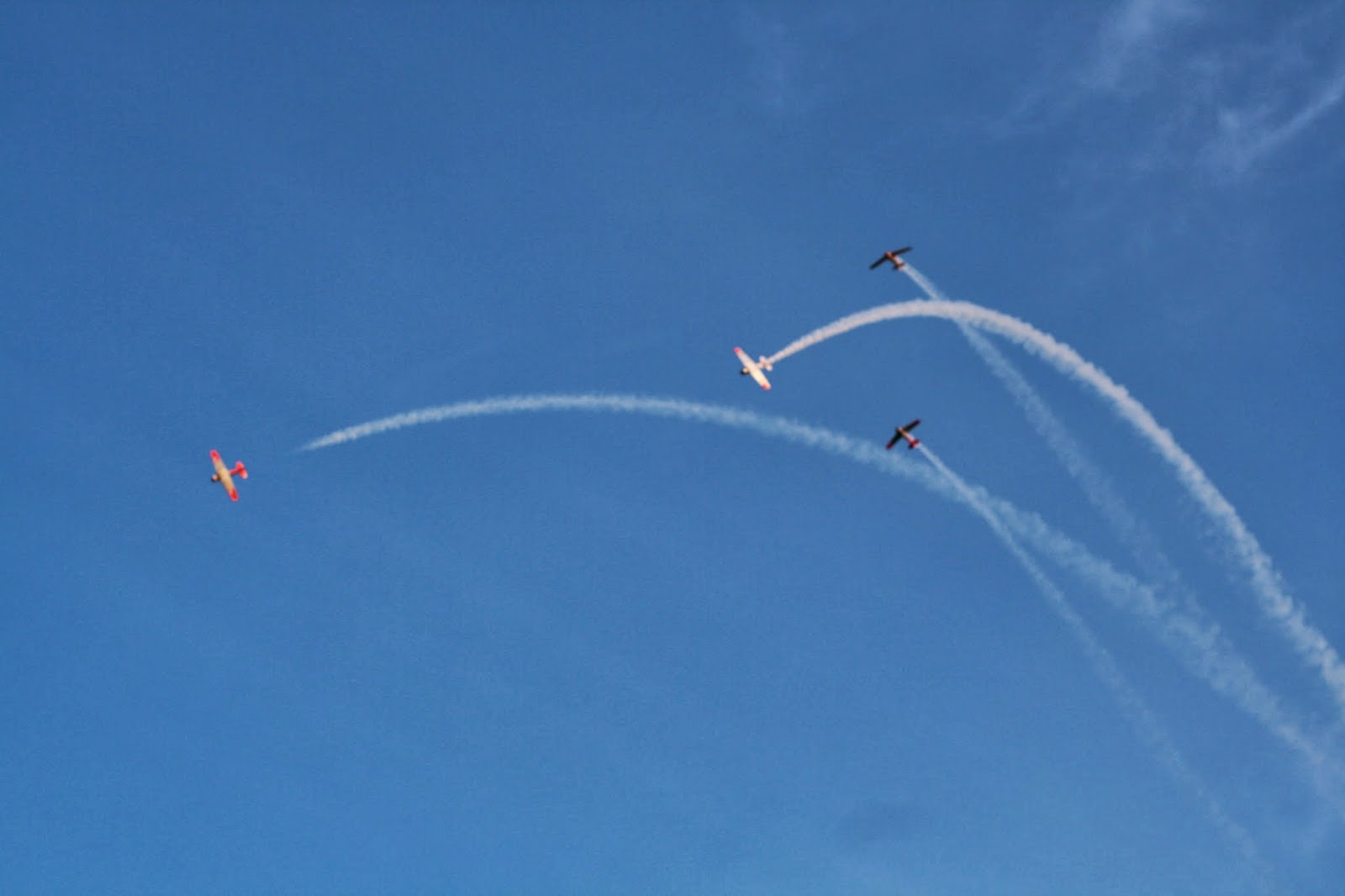 Four airplanes criss cross in a blue sky.
