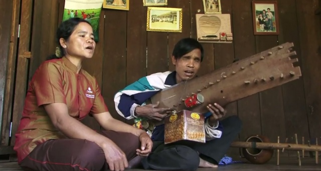 Création et réalisation de ce musicien non-voyant, cette cithare sur planche est probablement unique dans toute l'Asie du Sud-Est ! Elle reprend toutefois les principes de la cithare tubulaire avec ses cordes mélodiques et d'accompagnement. Ici, les cordes sont réparties de part et d'autre de la planche. Nyel Che est à la fois auteur, compositeur, arrangeur et interprète.  Une réalisation de © Patrick Kersalé