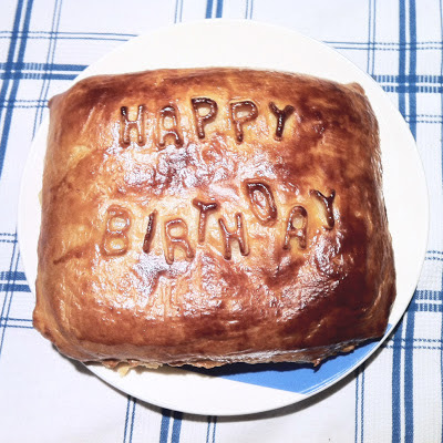 A large pastry on a plate with pastry letters spelling out Happy Birthday.