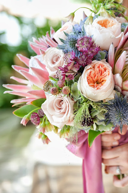 Exotic King Protea, Juliet Garden Roses, Astrantia, Poppy Pods, Agapanthus, Explosion Grass, Thistle, Leucadendron bouquet with silk ribbon.