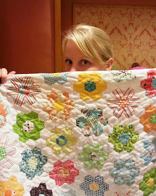 a woman's face peeking out behind a hexagon flower quilt she is holding
