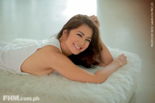 Alice Dixson in bed, smiling.