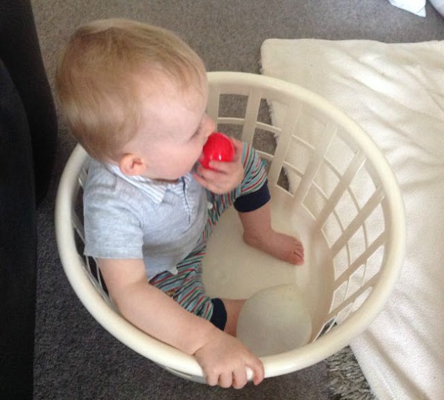 Baby sitting in washing basket licking a red toy ball