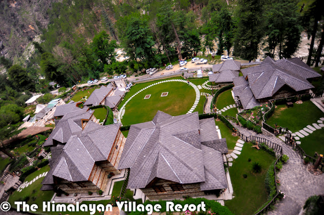 Want to enjoy Chamba, Kinnaur, Mandi, Kangra, Shimla, Spiti, Lahaul and Kullu at the same time? No I am not kidding! You could actually do that at the Himalayan Village Resort.And these are names of the cottages in the quaint resort, and captured the flavors of Himachal – the interiors, the food, entertainment-under one roof The resort, set amidst thick Deodar forest, helps you rediscover yourself, The serene mountain landscape of the land of gods and the unique architecture of Himalayan village resort- made of stone and wood-is so captivating that you many not want to go back to the city and its choresThe resort has been built in the ancient Kathkunia style –dry stacking stones and wood without cement. The inner walls are mud plastered to retain the native rustic charm. The resort is Eco-friendly and gives you an insight in the local customs and traditions. There are 8 cottages including two Machan- style rooms.The decor theme of each of the 750 sq ft cottage is built around the different culture flavors of Himachal Pradesh the decor of each room has been done up thematically, reflecting the tradition and culture of the state –deodar wood work, beautifully carved teak furniture, handmade Tussar silk curtains and traditional brass fittings give each room a cozy feel as you have come home. The resort provide daily housekeeping and evening turn down services.All cottages are equipped with a king size bed,4-seater sofa, study, mini Fridge ,mini bar, separate dressing area, fully furnished and equipped toilets and personal lawn. They also have private sit-outs. Lahaul and Kullu the Machan –Style cottages are the USP of the resort. They offer a sweeping view of the mountain landscape. Book the machans well in advance as they are most sought-after cottage because of their unique setting. The resort has mult-cusine restaurants, a well done up cozy bar that stocks finest liquor from around the world and a fully equipped spa to pamper you. The spa offers heat sauna, steam sa