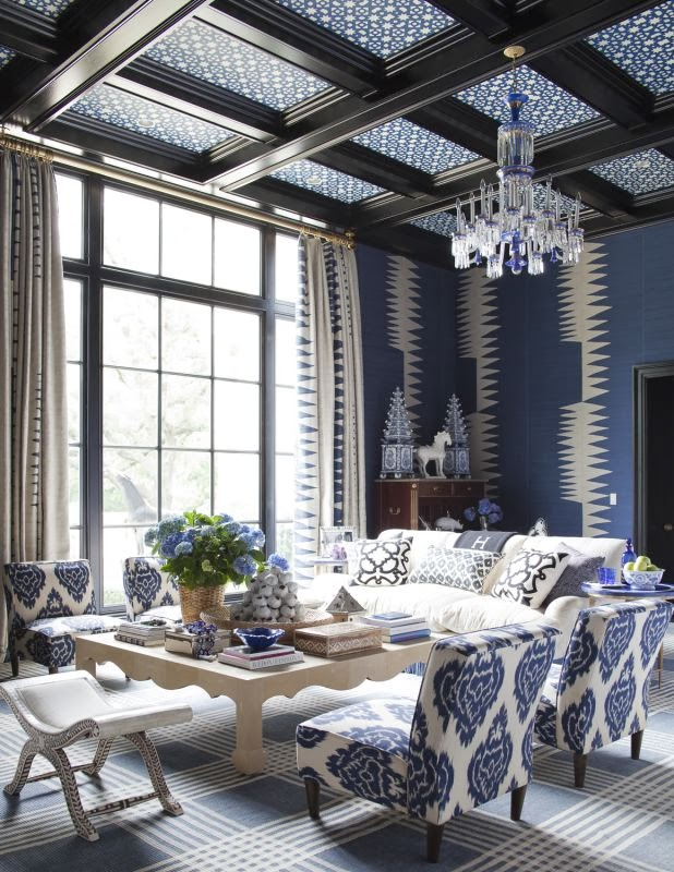 Blue living room with graphic print wall coverings and arm chairs, blue and white chandelier and patterned ceiling