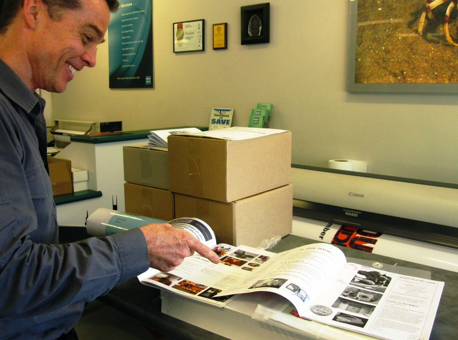 Man in a printers, pointing at two magazine issues.