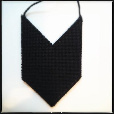 Back of embroidered geometric necklace made from plastic canvas. Bagsiden af broderet geometrisk halskæde af plastik kanvas.
