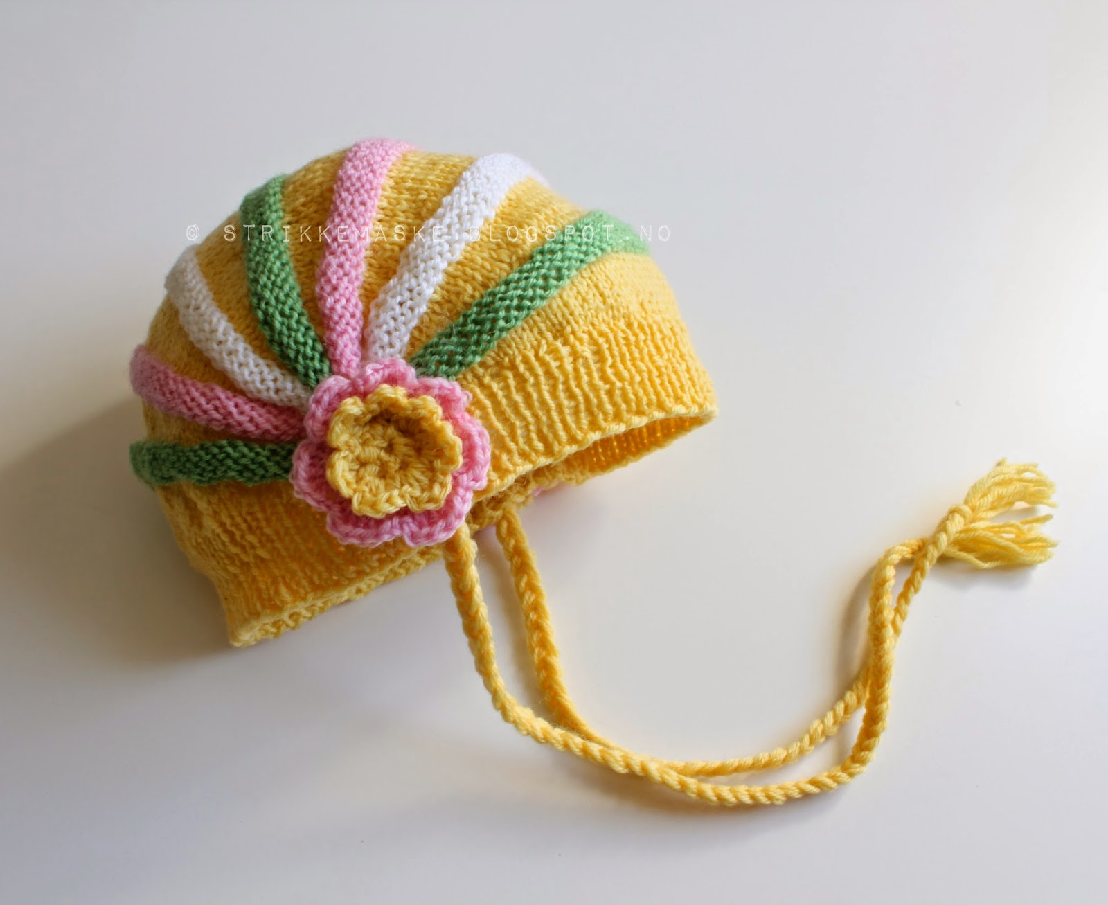 Strikka barnelue i gult med rosett og striper