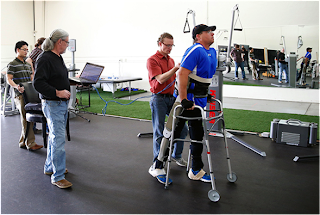 Test session of the exoskeleton: The test subject, Brian Shaffer, is followed by Shepherd Center  physical therapist Scott Hawes, Vanderbilt engineer Don Truex and Vanderbilt graduate  students Kevin Ha and Spencer Murray. (Mike Todd/Vanderbilt University)