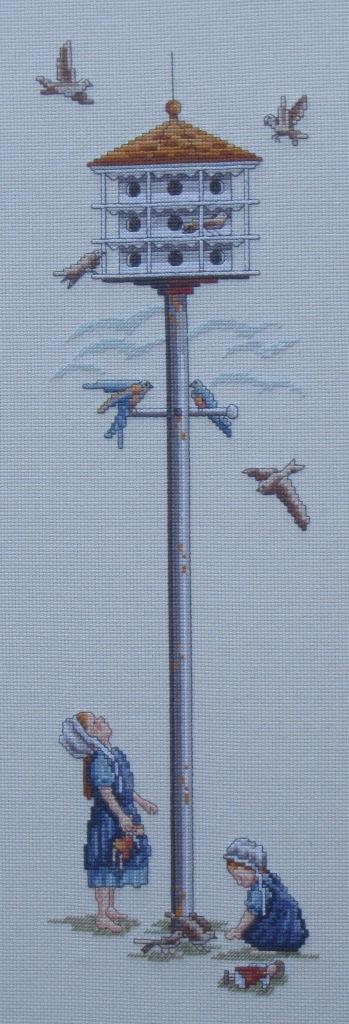 Cuadro de punto de cruz con pajarera y niñas alimentando a los pájaros