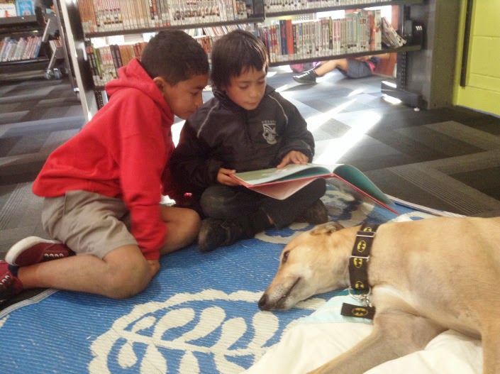 Two boys read to a dog.