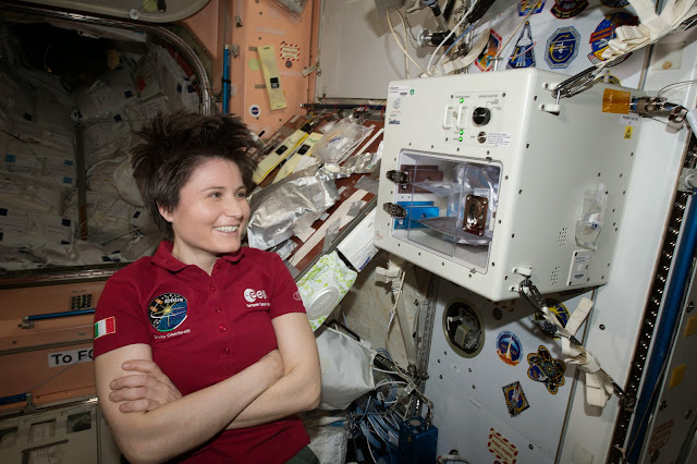 Samantha Cristoforetti waits next to the newly installed ISSpresso machine. The espresso device allows crews to make tea, coffee, broth, or other hot beverages they might enjoy. Image credit: NASA