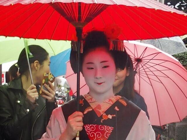 雨コートと赤い番傘の「とし恵美」さん。