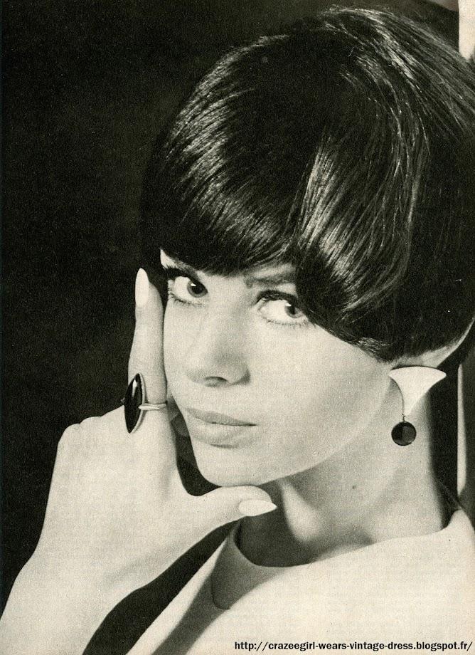 """The Knack ...and How to Get It .C'est une nouvelle façon d'avoir du """"pep"""". Cette année, cela s'appelle avoir le """"knack"""". Comment l a-t-on? Eh bien, regardez Anne. Oui, sur ces photos, c'est toujours Anne, diversement interprétée. L'auriez-vous reconnue?  Les secrets de ses transformations : des perruques, bien sûr, et des mèches postiches. Et, pour chaque coiffure, un bijou, un bijou unique mais choisi... pour donner le knack.PERRUQUE FRANGE : Une grosse frange droite de petit garçon. Coupe mathématique. Une barette, mais posée au ras du cou pour donner juste un peu d'humour à une robe noire toute simple. La perruque est une création de Maurice pour René Bourgeois. (Bijou J.-Ch. Brosseau, à La Mercerie.) PERRUQUE COLLÈGE-GIRL : C'est le charme. Un regard tendre, une coiffure sage, mais... la touche noire et blanche d'une barette biiou (J.-Ch. Brosseau) et les losanges  noirs et blancs du grand châle de laine (J.-Ch. Brosseau, à La Mercerie). La perruque mi-longue est de Bourgeois (création Maurice).  Ces perruques-là (celle-ci et la première) coûtent seulement 300 F. Cheveux naturels, trente teintes différentes. La coupe est faite sur vous, adaptée à votre visage et à votre tête. Il faut la nettoyer souvent. Pas la laver! Jamais d'eau ni de shampooing. Passez un coton imbibé d'alcool entre les mèches en frottant légèrement. Les cheveux seront souples et brillants .LA MÈCHE S.O.S.: Et voici encore trois autres visages d'Anne : ci-dessous, sage et sophistiquée. Ses cheveux (les vrais, mi-longs) sont tirés en arrière et remontés. La « couture» est cachée sous une petite mèche postiche. Coiffure et mèche Elrhodes. Les mèches en cheveux naturels existent dans toutes les couleurs (70 F). Boucles d'oreilles et broche du Printemps. LA PERRUQUE BOULE : Coupe ronde, mais une mèche un peu plus longue, un peu plus floue, donne le côté charme. La perruque est de Jacques Dessange. En cheveux naturels et en dix couleurs différentes . Elle coûte 390 F . ( bague Elysée-Store , boucl"""