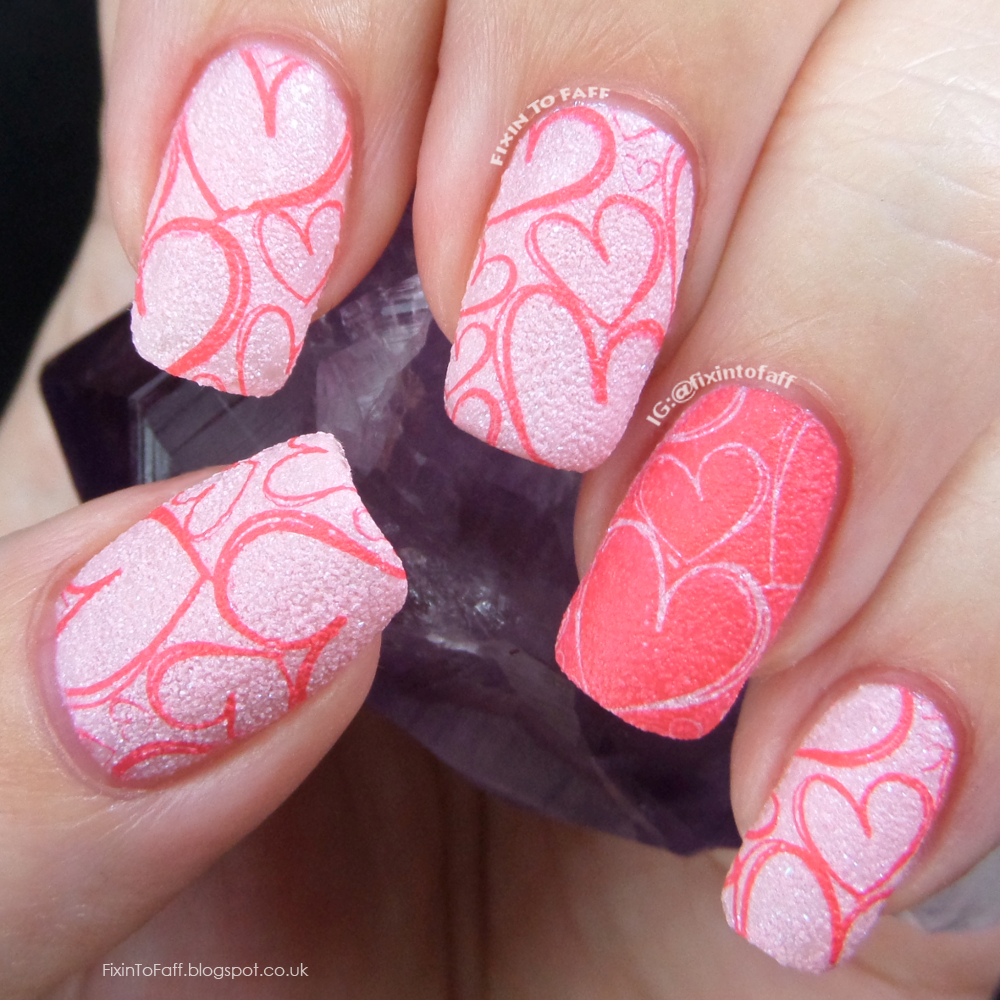 A textured pink and coral stamped Valentine's Day nail art of full-nail heart images.