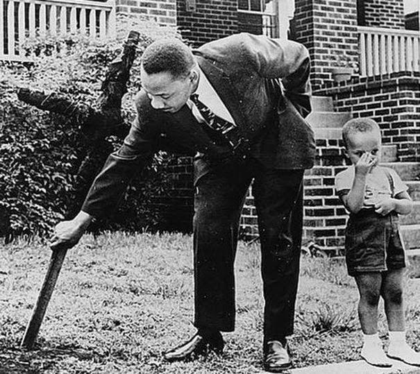 Мартин Лютер Кинг с его сыном убирающие обгоревший крест во дворе их дома, 1960 г.