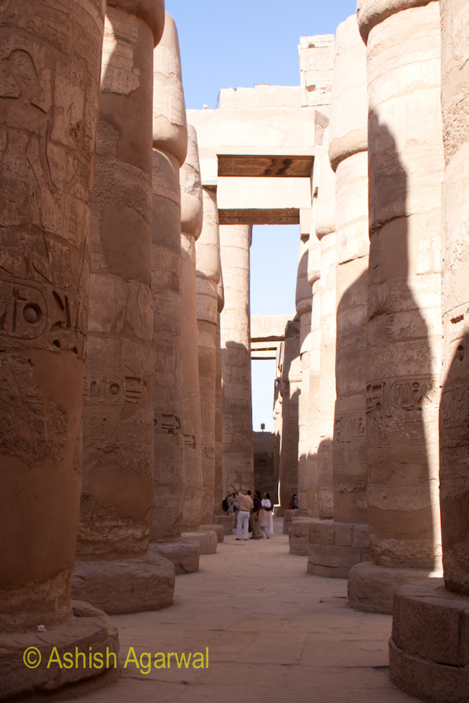 People standing at the base of the huge pillars of the Hypostyle Hall in the Karnak temple