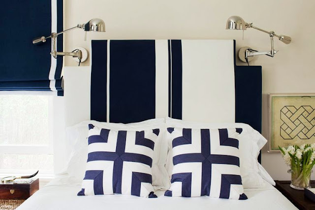 detail photo of a bedroom designed by Amanda Nisbet with blue and white pillows on a white bed with a navy headboard and navy Roman curtains with a single white stripe going down the side