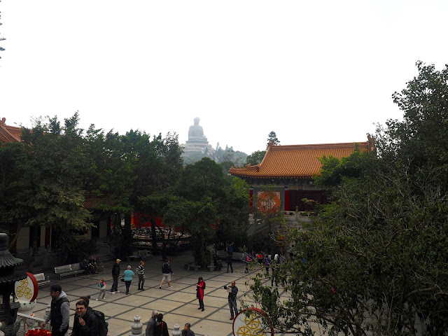View of Po Lin Monastery courtyard, with Big Buddha statue on the hill in the background, Ngong Ping, Lantau Island, Hong Kong