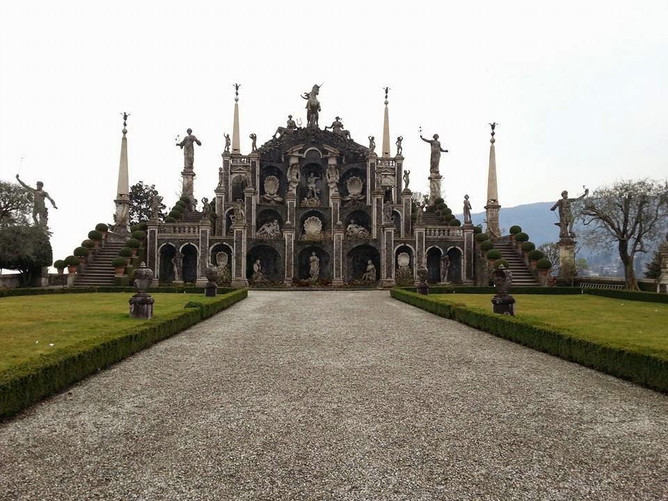 """Sinopse: Isola Bella ou """"Bela Ilha """"é uma das Ilhas Borromeu de Lago Maggiore , no norte da Itália. A ilha está situada no Golfo Borromeu 400 metros da cidade à beira do lago de Stresa. Isola Bella é de 320 metros de comprimento por 400 metros de largura e está dividido entre o Palácio , o seu jardim italiano , e uma pequena vila de pescadores. A ilha atingiu o seu mais alto nível de sucesso social durante o período de Giberto V Borromeo (1751-1837), quando convidados incluíram Edward Gibbon, Napoleão e sua esposa Joséphine de Beauharnais, e Caroline de Brunswick, a princesa de Gales. Descrição: A foto mostra um altar a céu aberto em parte do jardim planejado da ilha. Em uma rocha em forma de chapéu, câmaras côncavas de aberturas em arcos, escalonadas em três níveis, fazem parte da fachada em estilo barroco. Na parte central, esculturas brancas de deuses em formas humanas e grandes conchas abertas que remetem a leques, posicionadas de forma intercalada, decoram cada câmara. No topo, ao centro, há uma escultura imponente de um unicórnio com as patas dianteiras em salto com duas esculturas sentadas, uma de cada lado. Colunas quadrangulares e simetricamente posicionadas, em ambos os lados de cada nível, sustentam esculturas em poses diversas, algumas são menores que outras. Na base, há uma fonte e plantas que adornam a arte inferior de três estátuas, a central está em pé e as outras, sentadas na direção dela. As laterais do monumento são simétricas, sendo a parte térrea mais extensa, o desalinho é piramidal, também com esculturas sobre as colunas. O monumento é cercado por quatro mastros  finalizados por uma ave com as asas abertas, pousada em uma esfera. Ao fundo, em ambos os lados, em perspectiva de subida, um corredor duplo de plantas podadas de forma redonda. À frente do monumento, o chão de cascalho fino delimitado por grama, vegetação baixa e podada que emoldura as laterais do caminho, em cada quina, uma escultura de concreto em forma de um grande vaso."""