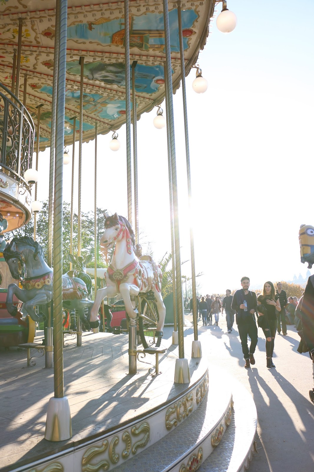 gorgeous photo of old world carousel in paris in the fall, lens flare of sun shine