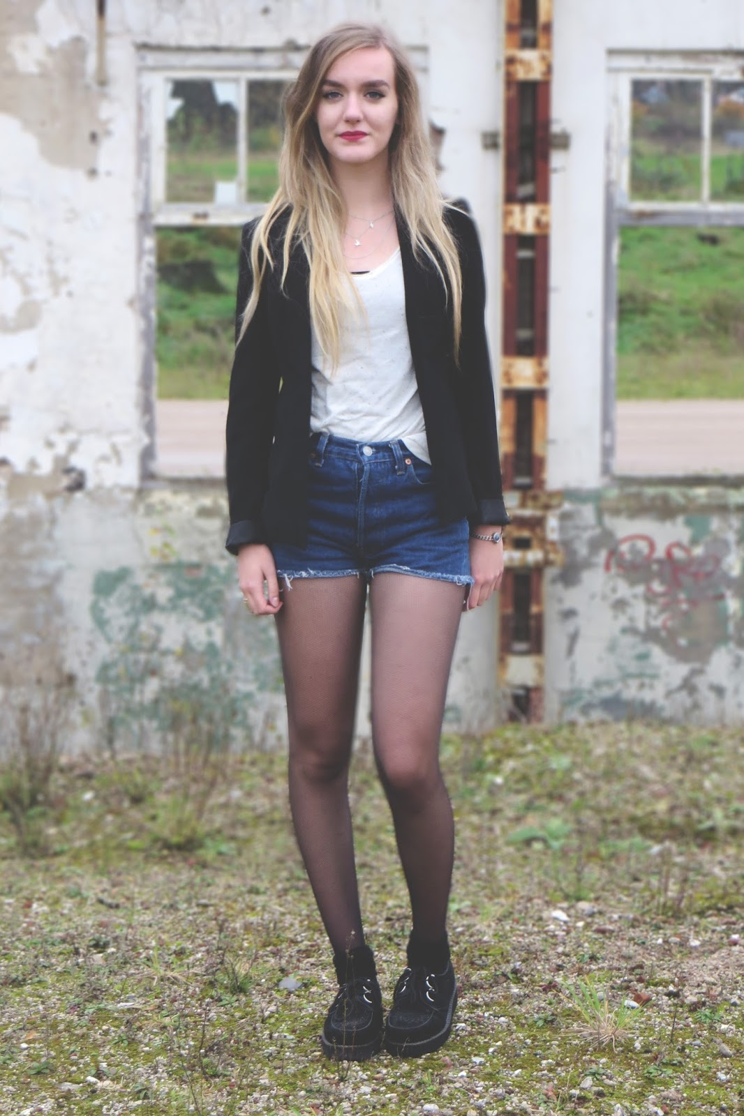 outfit with a black blazer, white top, shorts and creepers
