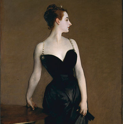 A woman in a black evening dress with a small amount of cleavage but her upper chest and neck exposed