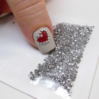 heart nail art with silver studs over Sally Hansen Ion