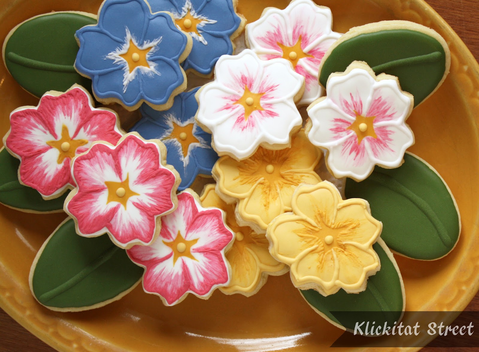 brush embroidery decorated sugar cookies iced to look like primrose flowers by Klickitat Street