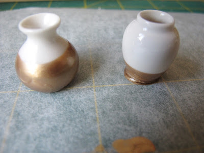 Two gold-dipped dolls- house white vases.