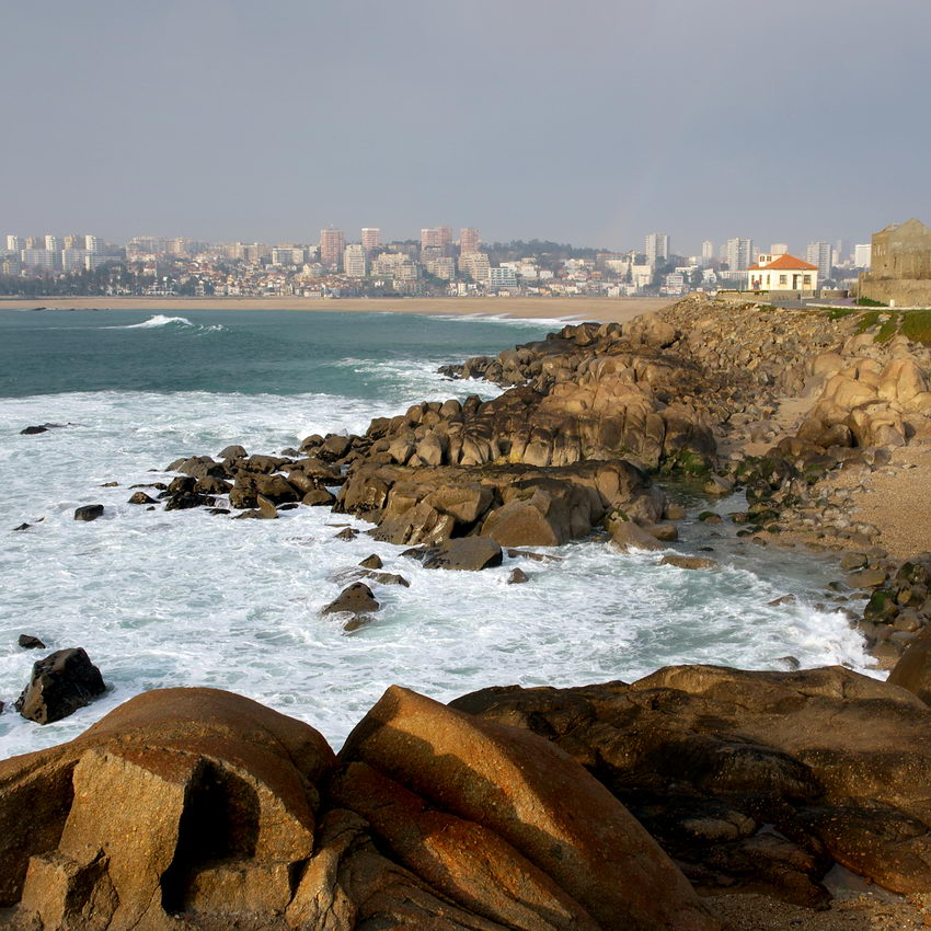 Foto da praia rochosa e da paisagem da Cidade do Porto em fundo