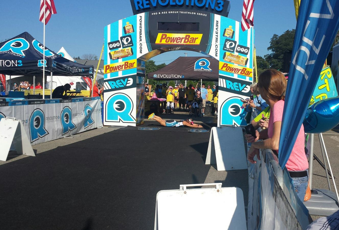 """Triathlete Jen Small does the """"Blazeman Roll"""" across the finish line at the REV3 Triathlon in Old Orchard Beach, ME, August 24, 2014."""