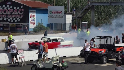 two-tone 1955 Chevrolet Belair doing burnout at racetrack