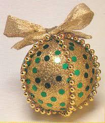 Bola navideña decorada con lentejuelas, escarchas, chaquiras y cinta
