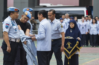 Dedy Romadi stripped of his prison guard jacket during dismissal ceremony.