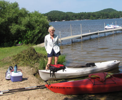 person standing beside two kayaks